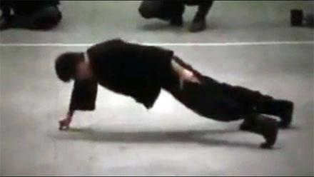 Bruce Lee realizando una demostración de flexiones a una mano, apoyando tan sólo un par de dedos.